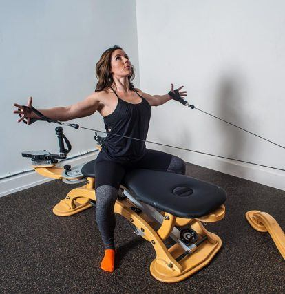 woman using GYROTONIC machine to stretch body