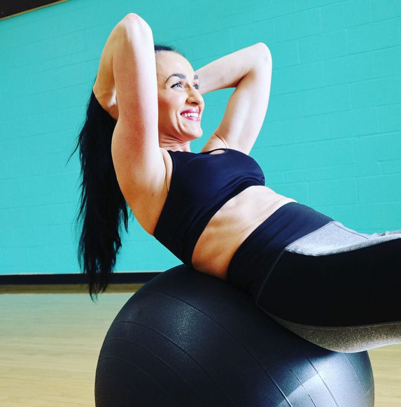 woman wearing workout attire and her hair in a ponytail doing sit ups while on large exercise ball