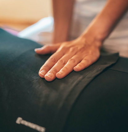 massage therapist pressing on small of client's back