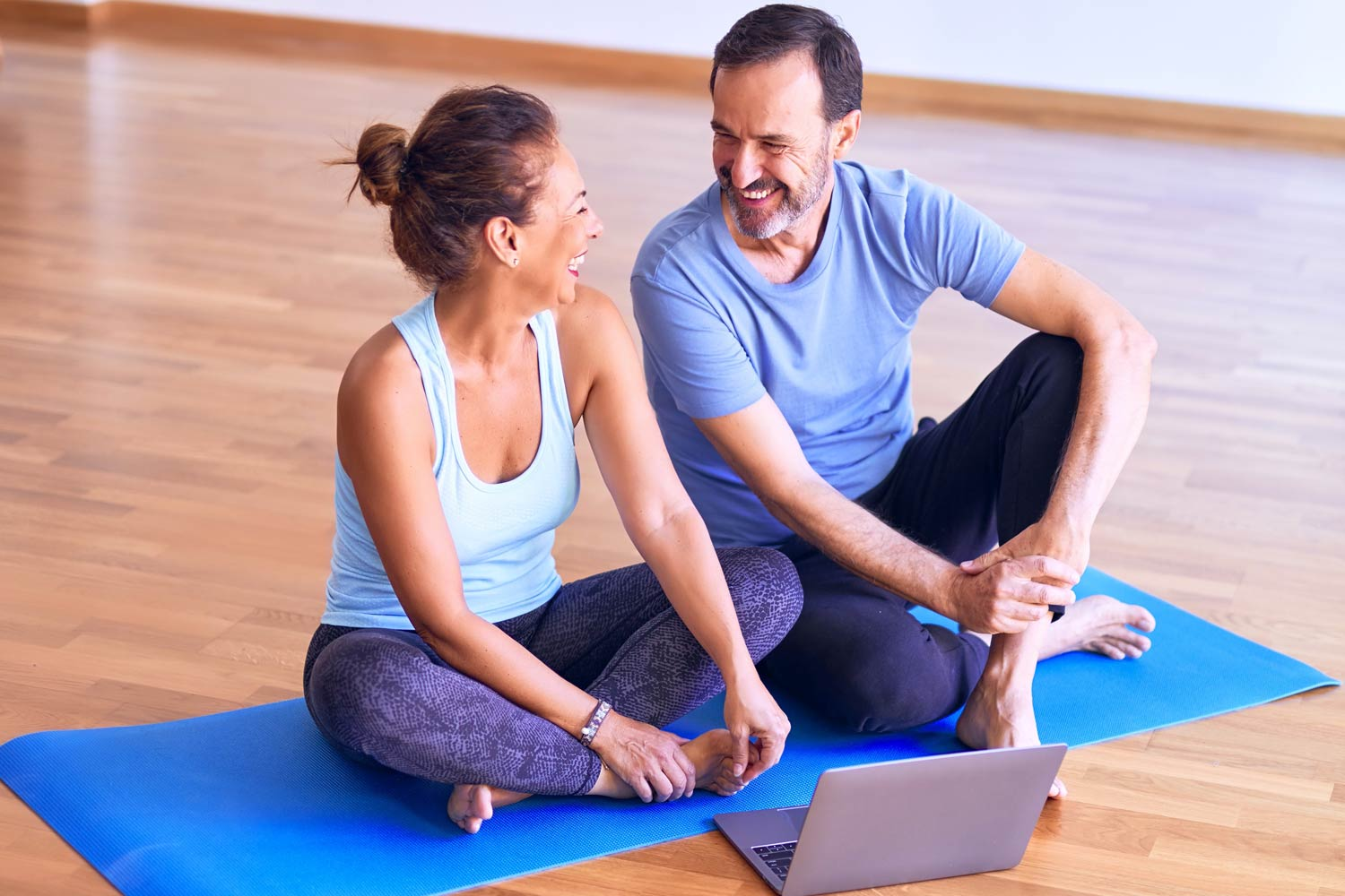 couple sits on yoga mat ready for pilates class over video call